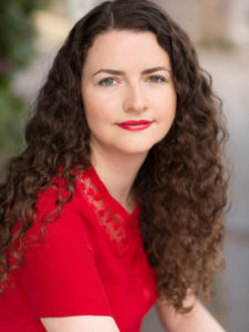 Belinda has long brown curly hair and is wearing a red top with matching red lipstick.