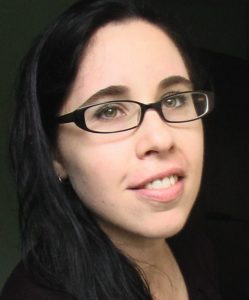 Bree has long dark hair and glasses. She is looking past the camera and smiling gently