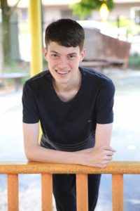 A teenage boy smiles at the camera. He has short brown hair and is wearing a black t-shirt.
