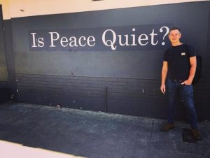 A man stands in front of a wall which has the words on it, Is Peace Quiet? The man wears jeans and a black t-shirt.