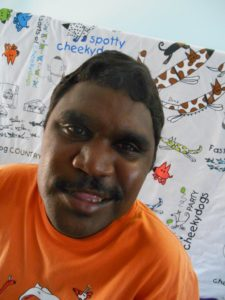 Dion has short hair and a moustache. He wears an orange shirt and is smiling to the camera.