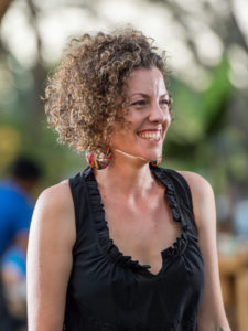 Johanna is slim with chin-length short brown curly hair. She is wearing a black top and big earrings and smiling.