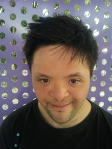 Josh smiles to camera. He stands in front of a purple dotted wall.