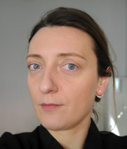 A woman looks to camera. She has brown hair tied back and blue eyes, and is in her mid thirties.