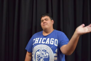 A man in his twenties stands on stage with a black curtain behind him. He wears a blue t-shirt with a Chicago motif. He has short dark hair.