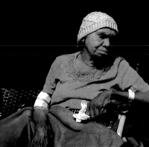 Black and white photo of a woman sitting in a share. She wears a dress and a knitted cap