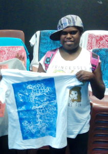 Photo of Abigail wearing a baseball cap. She is holding up a t-shirt with her artwork printed on it.