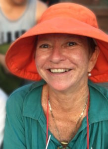 Photo of a smiling woman wearing a wide-rimmed orange hat