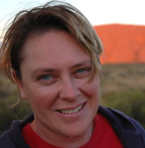 Photo of a woman with Uluru in the background