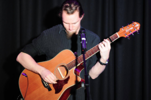 A man with short blonde hair and a beard plays acoustic guitar on stage with a microphone in front of him.