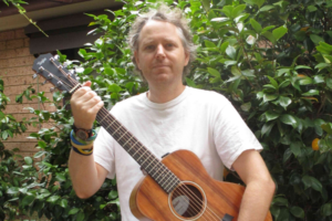 A man with grey hair tied back stands outside with an acoustic guitar.