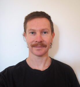 Headshot of a caucasian man in his 30s with slicked back red hair and a red moustache, wearing a black tshirt.