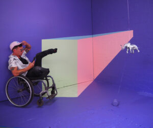 An interactive artwork showing purple walls and a white, pink and blue cube projected from a single point so that it looks as if the space is getting smaller. Bruno Booth sits in a wheelchair wearing a baseball cap and looks towards the disappearing point.