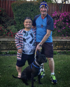 Two caucasian men and a dog. The man on the left wears a striped cardigan, a t shirt, backwards baseball cap, shorts, and has achondroplasia. The man on the right wears a beanie, a t shirt and shorts and he has his arm around the other man. The black dog sits on the ground between them.