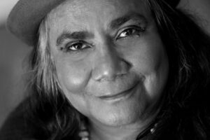 Black and white headshot of an Indigenous woman wearing a hat with light hair and dark eyebrows, gently smiling at the camera.