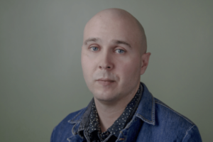 A bald man with white skin wearing a denim jacket looking serious.