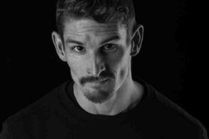 Black and white headshot of a man white short hair and a goatee.