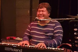 A man of Asian heritage in his 40s sits at a keyboard. He has short black hair, wears a striped jumper, and has his eyes closed as he sings into a microphone and plays the keys.