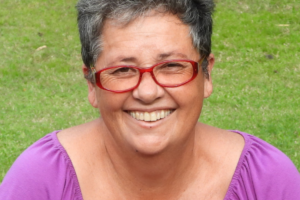 A woman of First Nations heritage smiles at the camera. She has short grey hair, red glasses, and a purple top.