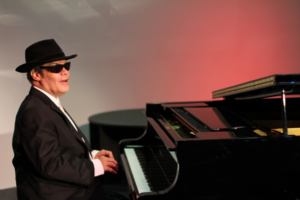 A man with white skin sits at a black grand piano, his hands on the keyboard. He has his mouth open, as if singing, and wears a black suit with a white shirt and black tie, a black hat, and black sunglasses.