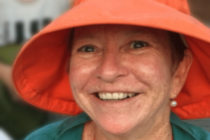 A woman with white skin wearing a large orange hat and smiling.
