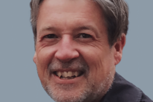 A man in his 50s with white skin and short grey hair and a grey beard, smiling.