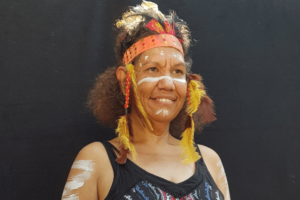 A woman of First Nations heritage in traditional dress and paint.