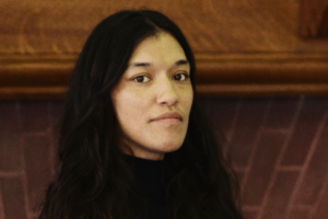A woman with long black hair parted in the middle, brown skin and brown eyes, looking serious.