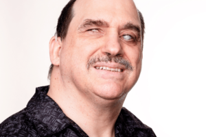 A man with white skin and short brown hair which is balding on top. He has a grey moustache and cloudy eyes and a hearing aid behind his visible ear. He is smiling.